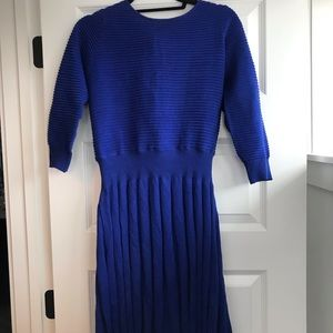Blue blouse and pleated skirt.